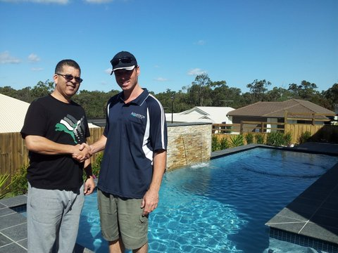Andrew and happy client by a new swimming pool
